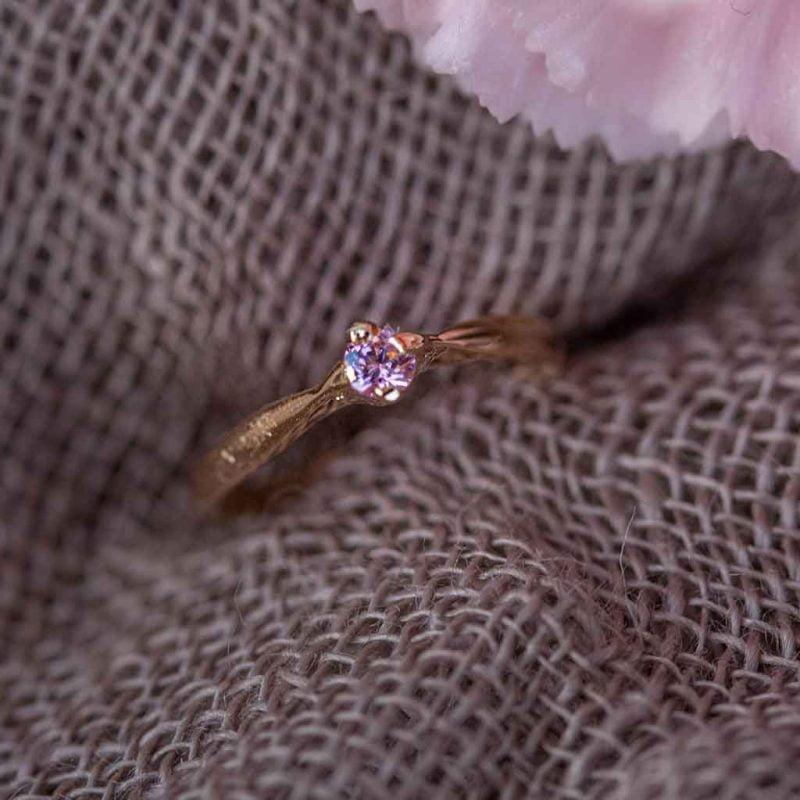 kultainen kastesormus vaaleanpunaisella kivellä